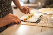 A Woman Preparing Homemade Sushi And Rolls. Forming Sushi. The Steps For Creating Sushi. View Of Pro poster