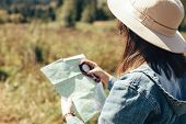 Stylish Hipster Girl Holding Map And Compass, Traveling In Sunny Mountains. Woman In Hat Exploring M poster