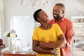 Mature married couple embracing in living room while looking at each other. Newly wed african couple poster