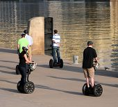 picture of segway  - Young people riding along on the sidewalk along the river - JPG