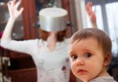 foto of comedy  - Portrait of scared baby against crazy mother with pan on head - JPG