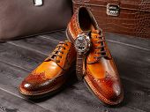 Classic Mens Shoes Of A Light Brown Shade Against The Background Of Mens Leather Briefcases poster