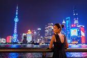 Shanghai city night lights glowing in dark sky. Elegant lady by the Bund river in fancy lace dress e poster