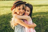 Outdoors Portrait Of Two Adorable Children Shares Love And Frienship. Two Little Girls Playing In Th poster