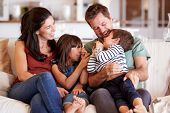 Mid adult white couple and their two young children sitting on a sofa at home smiling at each other poster