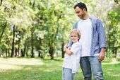 Handsome Father Hugging Adorable Son In Park With Copy Space poster