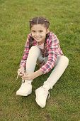 Tying Shoelaces. Girl Little Kid Spend Leisure Outdoors In Park. Girl Sit On Grass In Park. Child En poster
