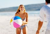 stock photo of beach-ball  - Young couple on a summer beach vacation playing with a beachball and having carefree fun - JPG