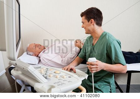 Young male radiologic technician smiling while looking at senior patient