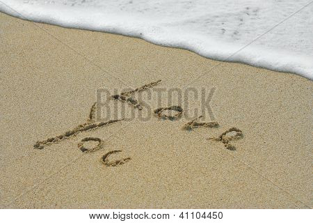 Concept or conceptual hand made or handwritten love you text in sand on a beach in an exotic island