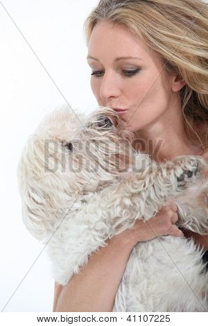 Middle-aged woman kissing dog.