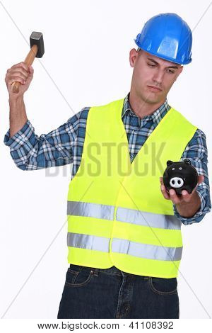 Construction worker breaking open a piggy bank