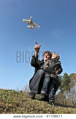 Father and son playing with toy plane in field