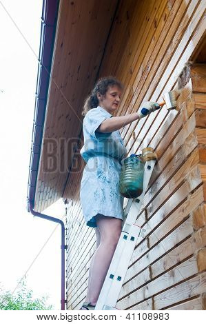 Pretty woman painting her house