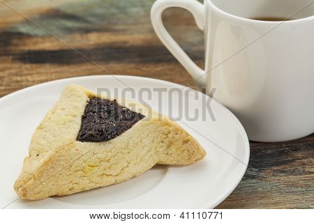 fruit hamantaschen cookie  on a plate with a cup of coffee - a traditional pastry in Ashkenazi Jewish cuisine for holiday of Purim