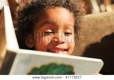 Young Mixed Race Boy With Curly Hair Reading