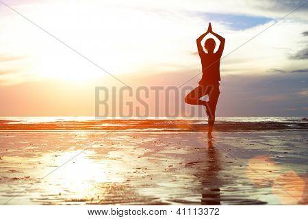 Joven practicando yoga en la playa al atardecer