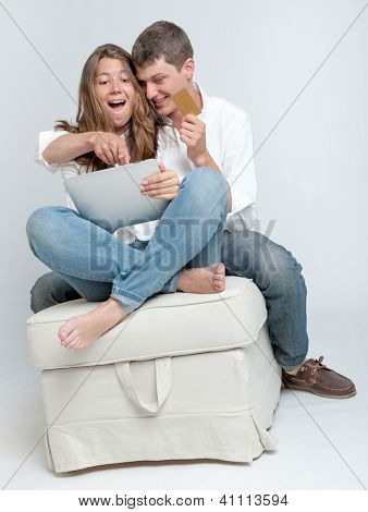 Young couple sitting together with a tablet pc and a credit card