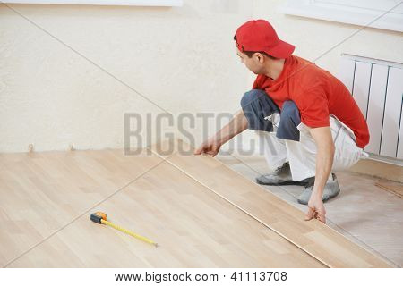 carpenter worker installing wood parquet board during flooring work