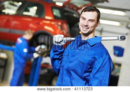 Mecânico de automóveis reparador jovem inspecionar o carro durante a manutenção do automóvel no motor auto reparo sho