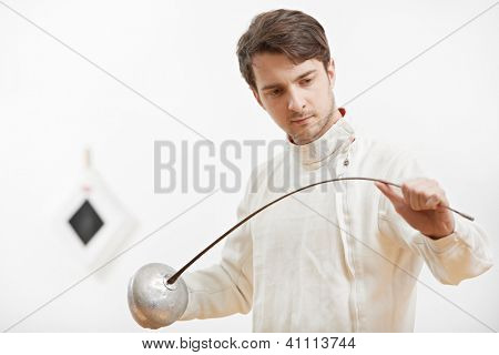 Young fencer in protective sport wear inspecting rapier foil