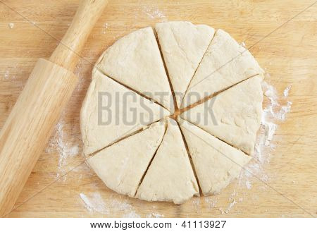 Scottish girdle scone  (or griddle scone) dough after rolling out and cutting into wedges on a chopping board.