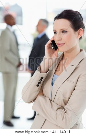 Serious businesswoman talking on a mobile phone with executives behind her