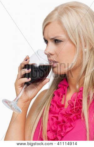 Serious blonde drinking a glass of wine against white background