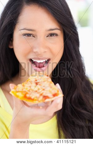 A close up shot of a woman about to eat pizza as she looks at the camera