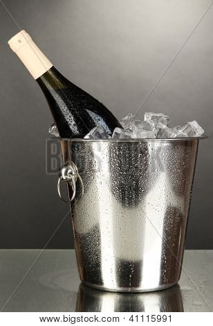 Bottle of wine in ice bucket on black background