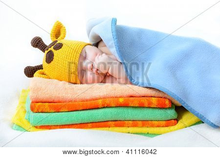 cute sleeping baby boy in funny hand made giraffe hat, beautiful kid dozing on pile of colorful towels with blue plaid, studio shot