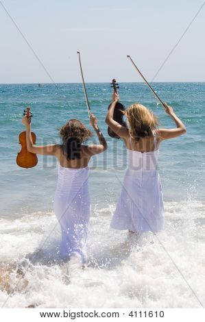 Two Violinist Play On Beach Water