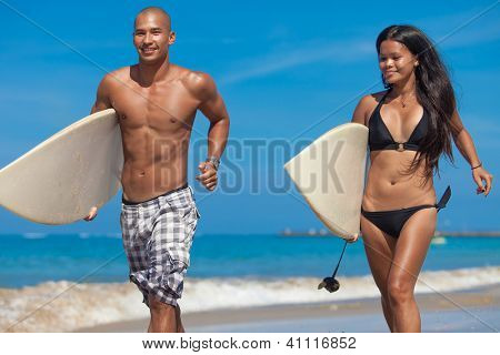Young couple running on beach with surfboards in arm
