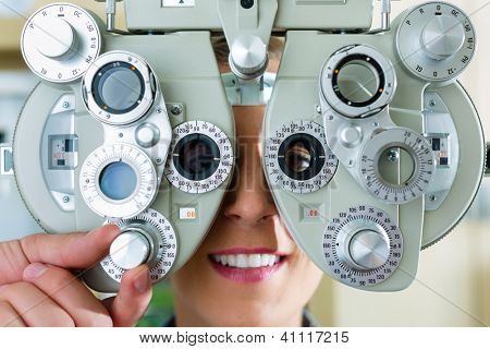 Young woman at phoropter at optician or ophthalmologist for eye test, she is near-sighted or long-sighted