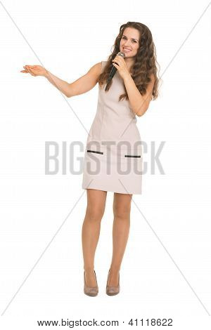 Happy Young Woman With Microphone Pointing On Copy Space