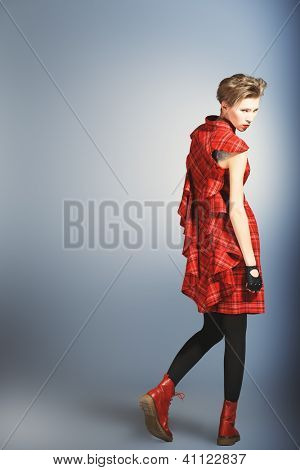 Young fashionable model posing at studio with expression.