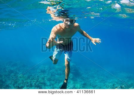 Young Man Snorkeling Underwater over Tropical Reef in Hawaii