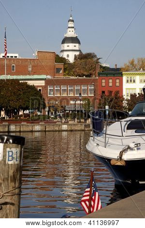 ANNAPOLIS, MD - OCT 21: A boat moored at the city dock with colorful buildings and the Maryland State House in the background on October 21, 2012 in downtown Annapolis, Maryland.