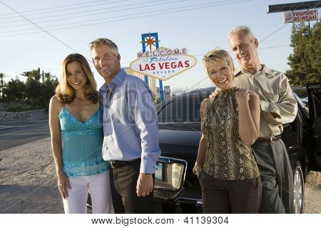 Two couples posing in front of Welcome to Las Vegas sign, group portrait
