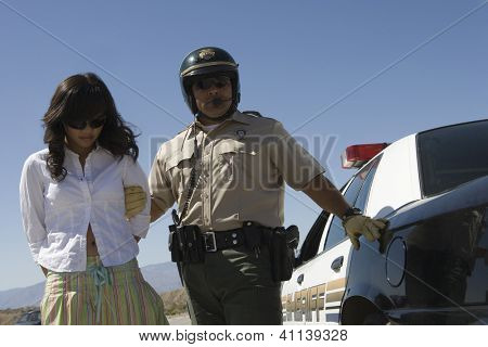 Police man arresting young woman on road