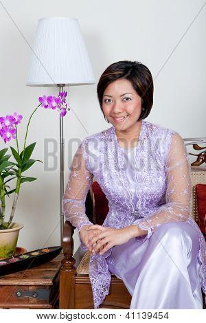 Bela jovem mulher malaia em rosa baju kurung, um traje tradicional.