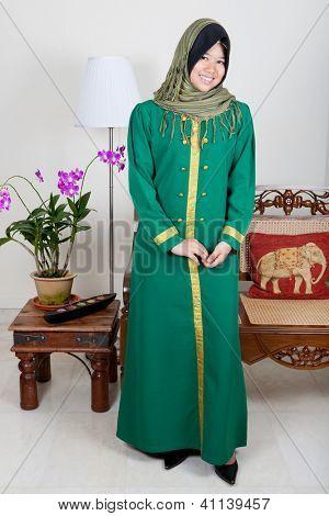 Bela jovem mulher malaia em terno verde, um traje tradicional.