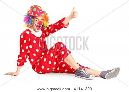 A clown with smiling joyful expression sitting down and giving thumb up isolated on white background