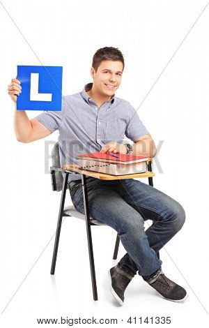 A young student sitting on a school chair and holding a L plate isolated on white background