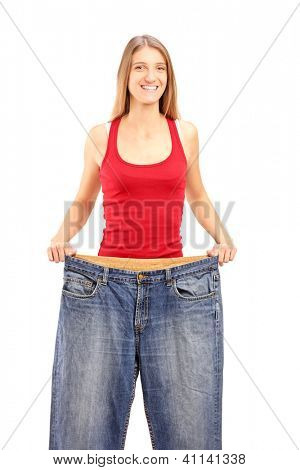 A weight loss female showing her old jeans isolated on white background