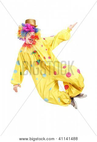 Full length portrait of a male clown jumping isolated on white background