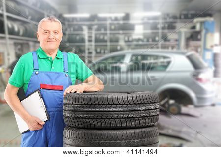 Mature auto mechanic posing on a tires in front of car during automobile maintenance at auto repair shop