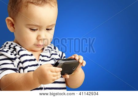 Portrait Of Baby Boy Using Cell Phone against a blue background