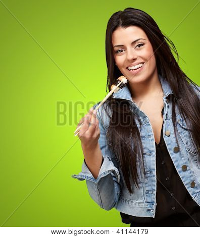 Young Woman Holding A Piece Of Sushi With Chopsticks On Green Background