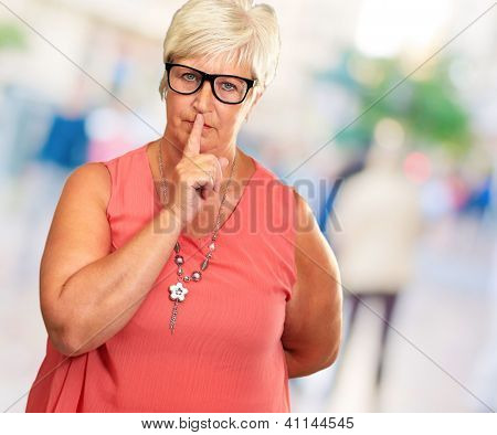 Senior Woman With Finger On Lips, Outdoor